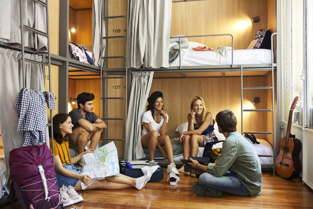 Young friends planning trip in hostel
