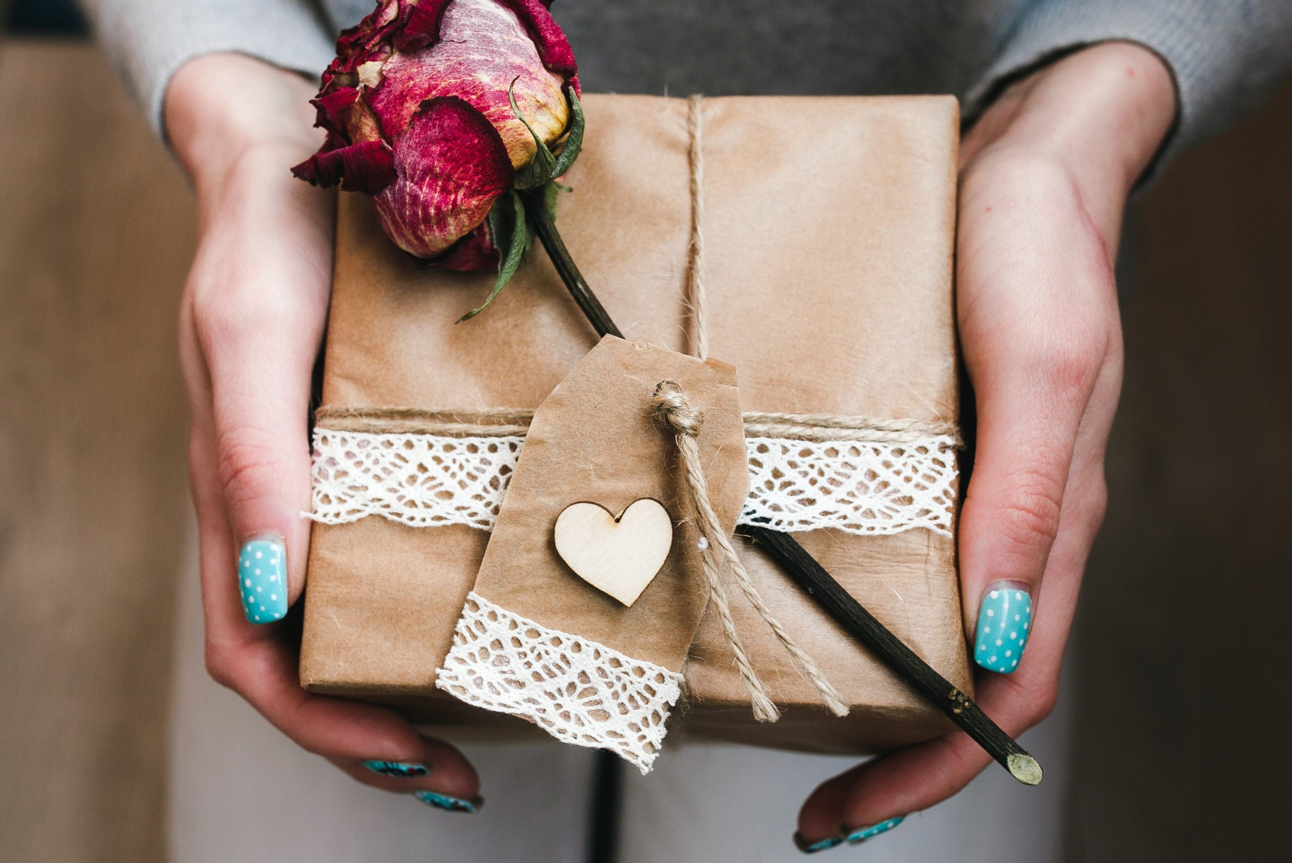 woman-holding-wrapped-gift-with-rose-brown-wrapper